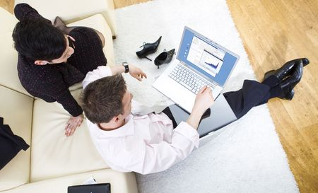 Businessman sitting on floor and teamworking on laptop computer with businesswoman. They look workoholic. High-angle view. Stock Photo - 3868599