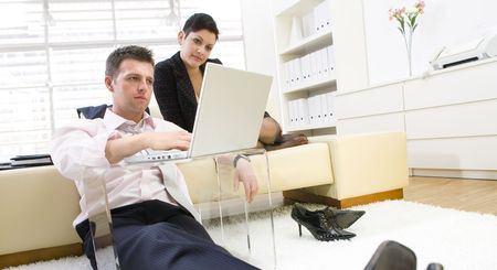 Businessman sitting on floor and teamworking on laptop computer with businesswoman. They look workoholic.  Stock Photo - 3868533