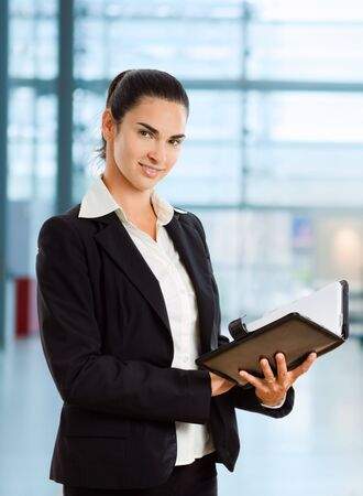 Attractive businesswoman looking at day planner in office lobby. Stock Photo - 3868532