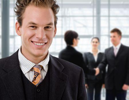 together with long tie: Equipo de gente de negocios, empresario al frente, handsake en el fondo.