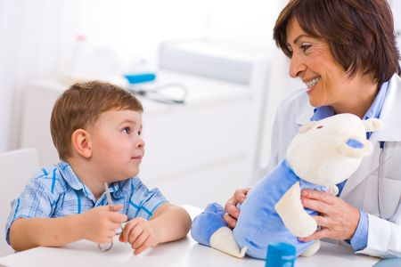 Senior female  pediatrician playing with child at doctors office. Stock Photo - 3868584