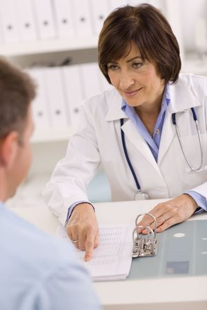 Smiling senior female doctor talking with male patient at office. Stock Photo - 3868534
