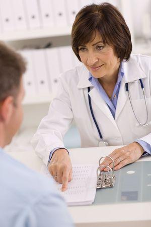 doctora: Smiling senior femenino m�dico hablando con paciente de sexo masculino en la oficina. Foto de archivo