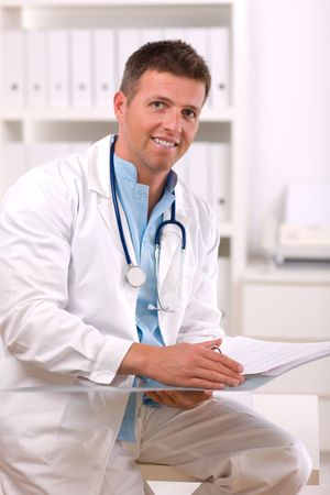 Happy male doctor working at office, smiling. Stock Photo - 3868585