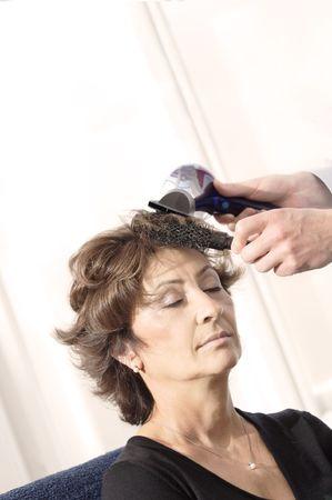 hairdresser parlor: Senior woman having haircut in barber shop. Stock Photo