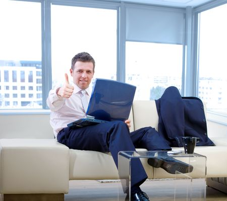 compute: Happy successful businessman sitting on couch at office, working on laptop compute, smiling and showing thumb-up.