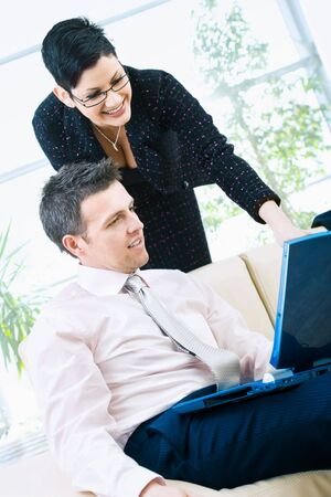 Happy businessman and businesswoman working together on laptop computer at lobby, smiling. Stock Photo - 3884364