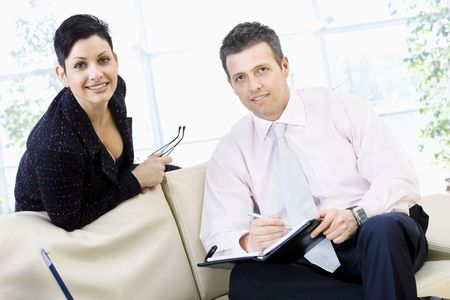 Happy businesspeople sitting of couch at office and  teamworking, they looking up to camera and smiling. photo