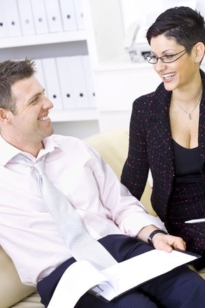 Businessman and businesswoman working together, stitting on sofa looking at financial figures, smiling. photo