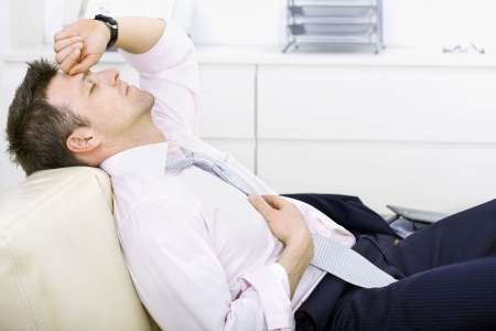 tired eyes: Mid-adult businessman lying on sofa at office, looking tired, eyes closed. Bright background. Stock Photo