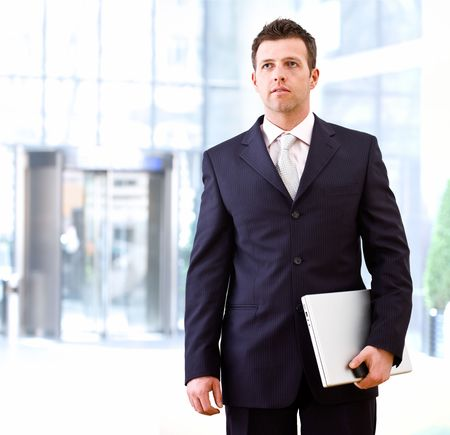 officetower: Determined successful businessman standing and holding laptop computer in hand, outdoor in front of office building.