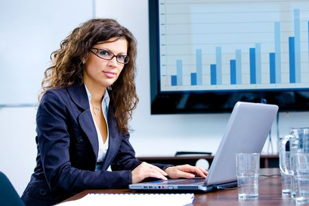 Young happy businesswoman working on laptop computer in meeting room at office, looking at camera smiling. photo