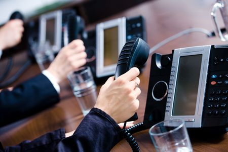 Close-up of hands holding landline phone recievers at customer service office. photo
