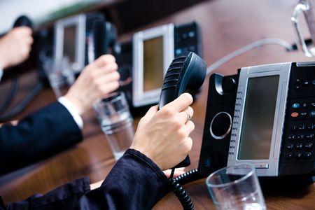 repondre au telephone: Gros plan de mains tenant des r�cepteurs de ligne de t�l�phone fixe � un bureau de service � la client�le. Banque d'images