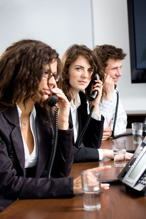 Young customer service operator team working at office, holding phone, calling, giving helpdesk support. Stock Photo - 3884368