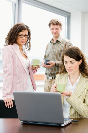 Team of young successful office workers talking and drinking coffee at meeting room, businesswoman working on laptop computer in front. Stock Photo - 3884365