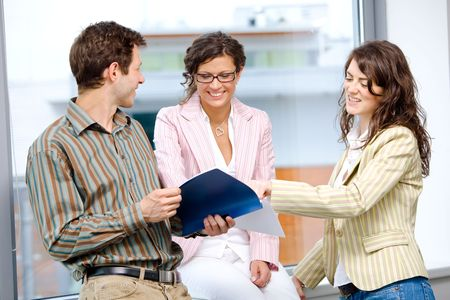 Happy young business people having team meeting at office and reading documents, smiling. Stock Photo - 3884420
