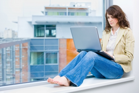Young businesswoman sitting at office window, thinking and working on laptop computer. Stock Photo - 3884404