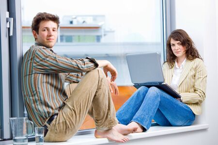 Businessman and businesswoman having creative meeting,  sitting in office window working on laptop computer and talking. photo