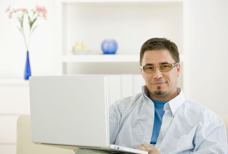 teleworking: Happy casual man teleworking using laptop computer at home.