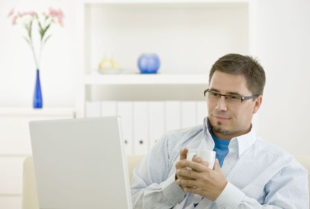 outworking: Happy casual man using laptop computer at home drinking coffee. Stock Photo