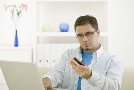 Casual man at home using laptop computer purchasing by credit card. photo