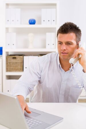 outworking: Business man working on computer at home calling on phone.