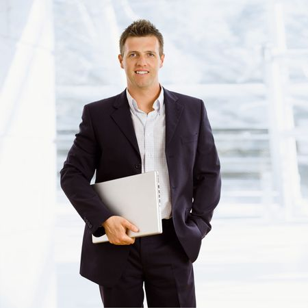 Happy businessman holding laptop computer indoor smiling photo