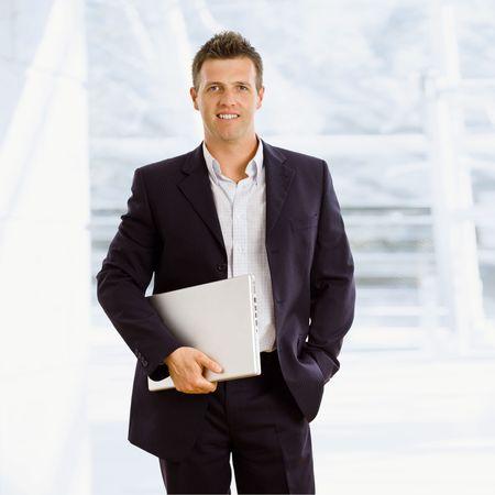 businesswear: Happy businessman holding laptop computer indoor smiling