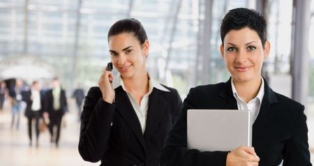 Happy businesswomen at office lobby calling on mobile phone holding laptop. photo