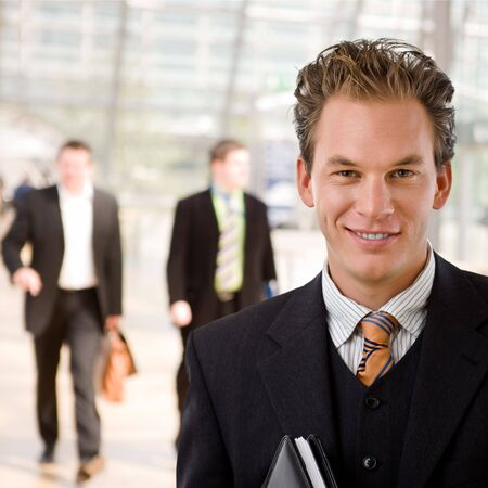 businesswear: Portrait of happy young businessman smiling at office. Stock Photo