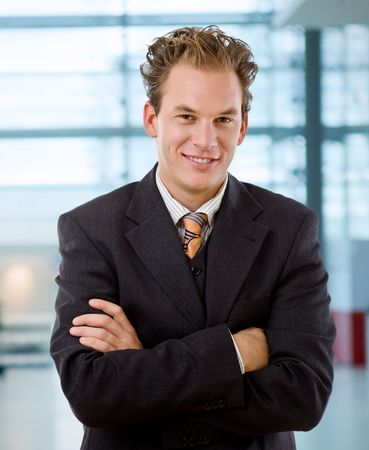 corporation: Portrait of happy young businessman smiling at office. Stock Photo