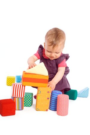 Cute baby girl (1 year old) playing with toy blocks, isolated on white. Toys are officially property released. photo
