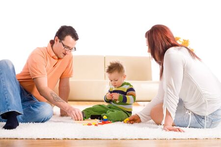 Family with baby boy ( 2 years old ) sitting on floor at home and playing together. Stock Photo - 3889269