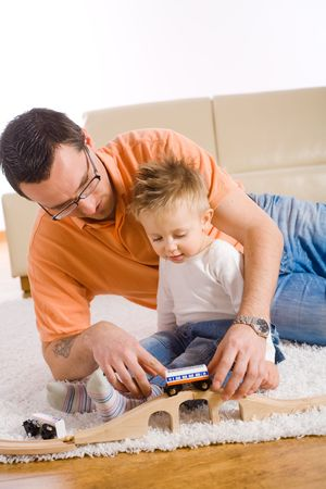 Young father and little baby boy playing together with toy train at home. photo