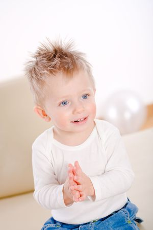 2 years old happy baby boy sitting on sofa clapping and smiling. Stock Photo - 3889259