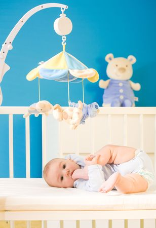 hanging toy: Infant baby resting and playing in his little baby bed at nursery. Toys are officially property released. Stock Photo