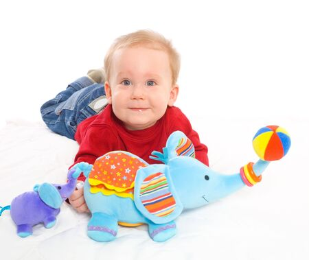 released: Happy baby boy (6 months old) playing with soft toys, smiling. Toys are property released. Stock Photo