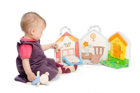 toy story: Baby girls sitting on floor playing with stuffed story book. Isolated on white. Toys are officially property released.