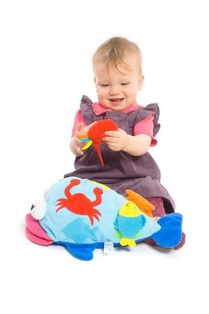 released: Cute baby girl (1 year old) sitting on floor playing with stuffed animal toy.  Isolated on white, smiling. Toys are offically property released.