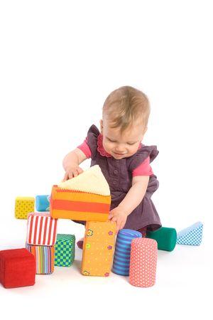 9 months old: Los juguetes son propiedad de edicion. Peque�a ni�a (9 meses de edad) jugando con bloques de juguete. Aislado en blanco. Foto de archivo