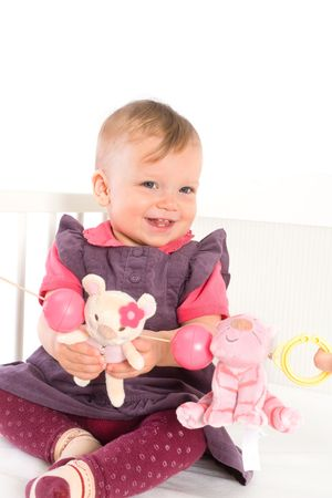 Cute baby girl (1 year old) sitting on crib, holding soft toys. Isolated on white, smiling. Toys are offically property released. Stock Photo - 3889299