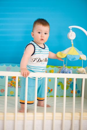 Baby boy ( 1 year old ) standing in baby bed at childrens room. photo