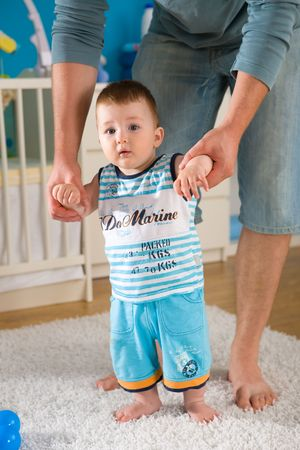 Baby boy ( 1 year old ) walking his first steps at children's room. Stock Photo - 3889301