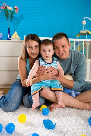 Portrait of happy family at home. Baby boy ( 1 year old ) and young parents father and mother sitting on floor and playing together at children's room, smiling. Stock Photo - 3889312