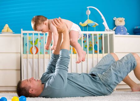 Father lying on back and lifting baby boy ( 1 year old ) at home in childrens room. photo