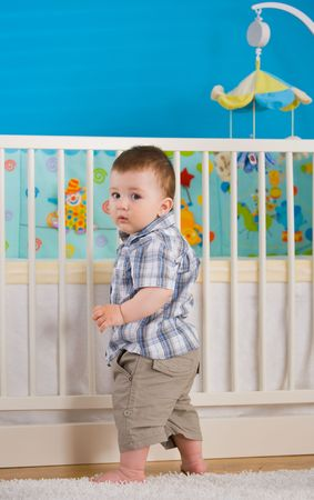 Sweet baby boy ( 1 year old ) standing at childrens room in front of crib. photo