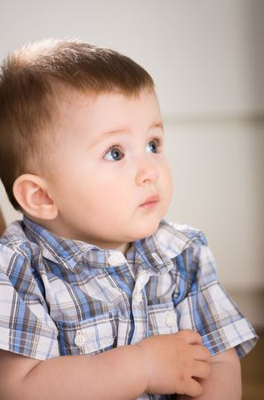 babyboy: Portrait of cute baby boy ( 1 year old ) at home, looking away.