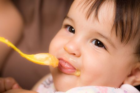 Mother feeding baby girl with spoon. Stock Photo - 3889293