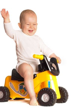 11 moths old baby rides a toy motorbike and he really enjoys it. Stock Photo - 3889256